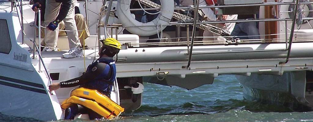 a man is pulled out of the water practicing crew overboard techniques