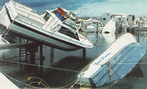 A boat injured by a Hurricane is suspended from a dock by a few docklines.