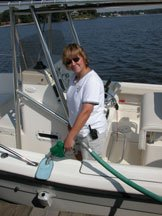 A young lady fills the fuel tank on her center console boat.