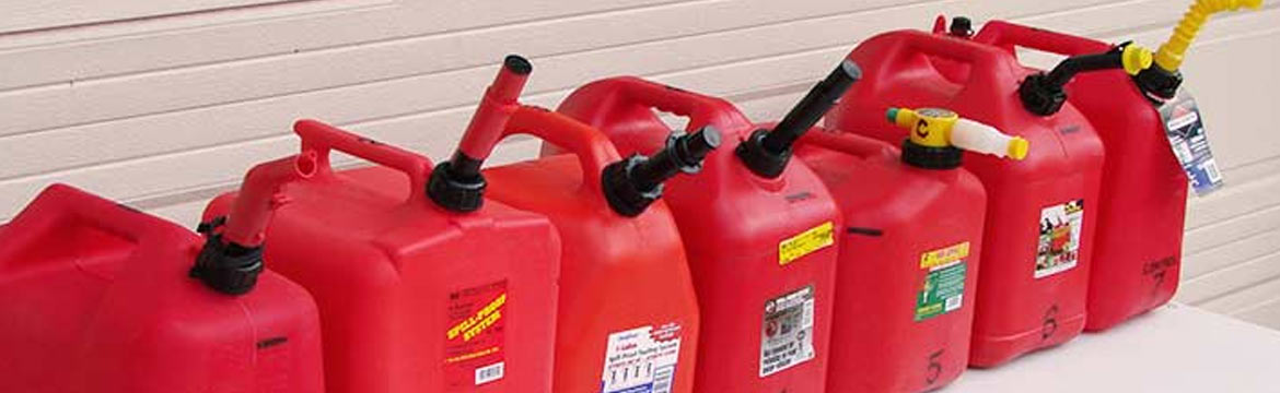 An assortment of red fuel jugs, also known as jerry jugs