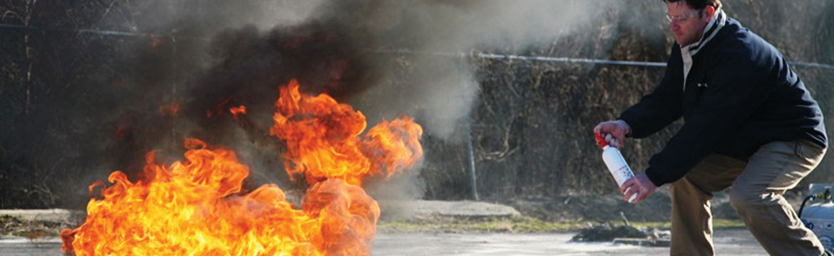 A man aims his fire extinguisher at a flame