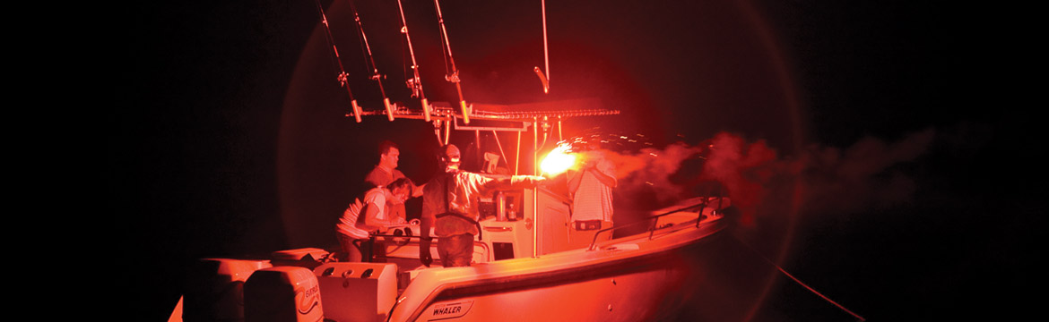 a boat at night with a red flare active