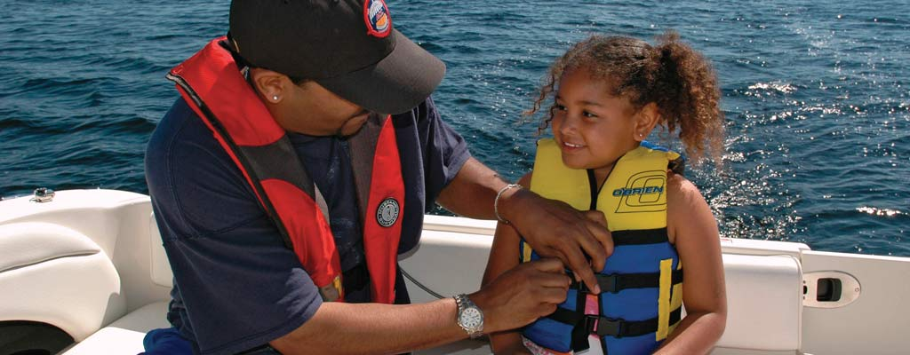 a man adjusts a girl's life jacket