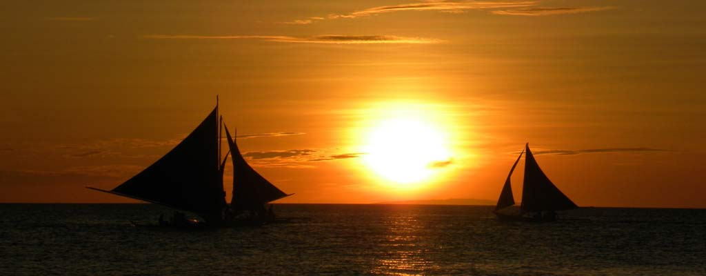 two sailboats pass eachother in front of sunset