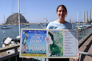A woman on a dock in California holds a sign which reads - Please Don't Dump...Use The Pumps.