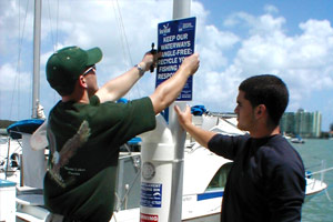 Two boys install a sign which reads, Keep our waterways tangle-free: Recycle your fishing line responsibly.