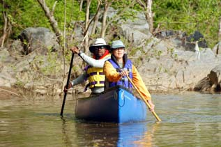 a couple people paddle a canoe