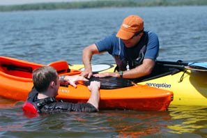 a man helps someone who has capsized his kayak