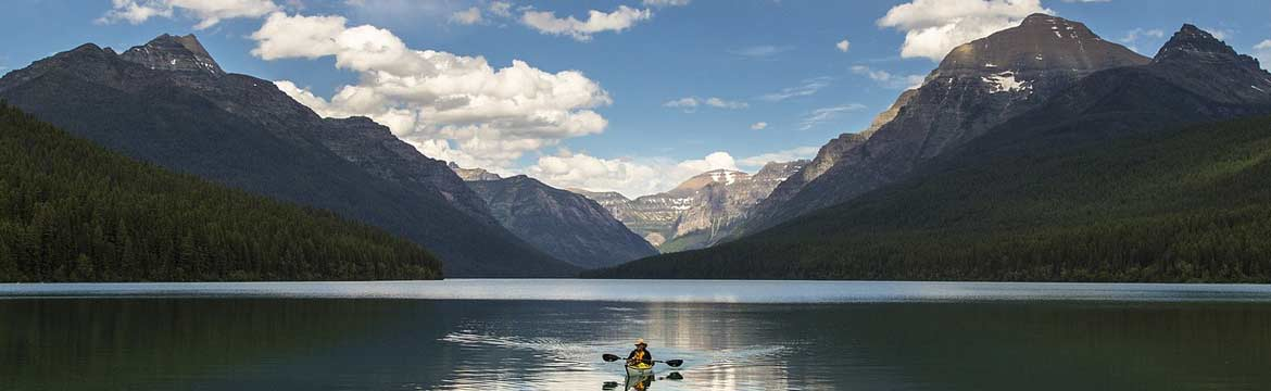 a person kayaking on a lake with large mountains behind