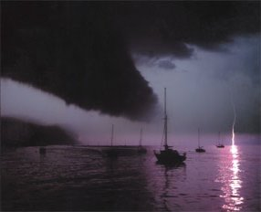 a very dark thunderstorm approaches some moored boats, while lightning is seen in the distance