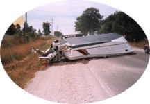 a boat that's fallen off a trailer on a road